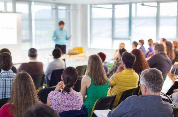 La foto mostra una aula di formazione con tante persone